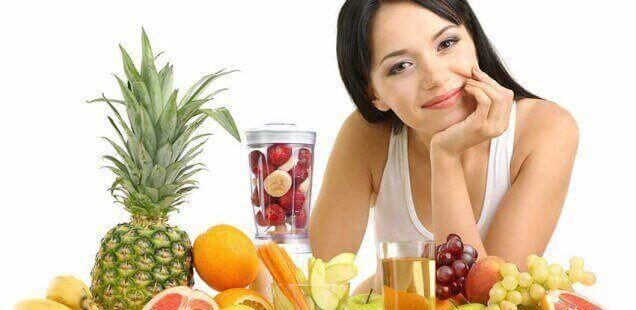 Frau mit Mixer und Obst